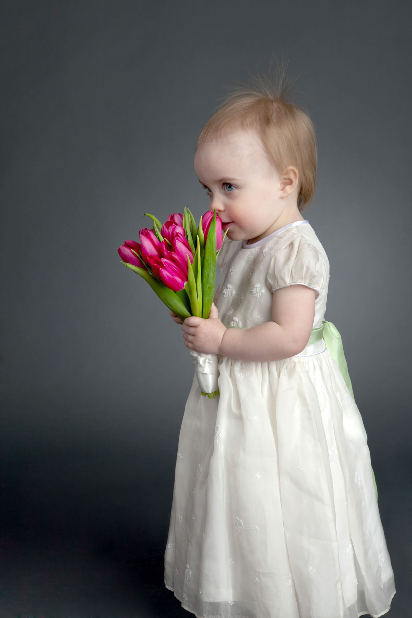 Young girl poses with tulips during portrait session