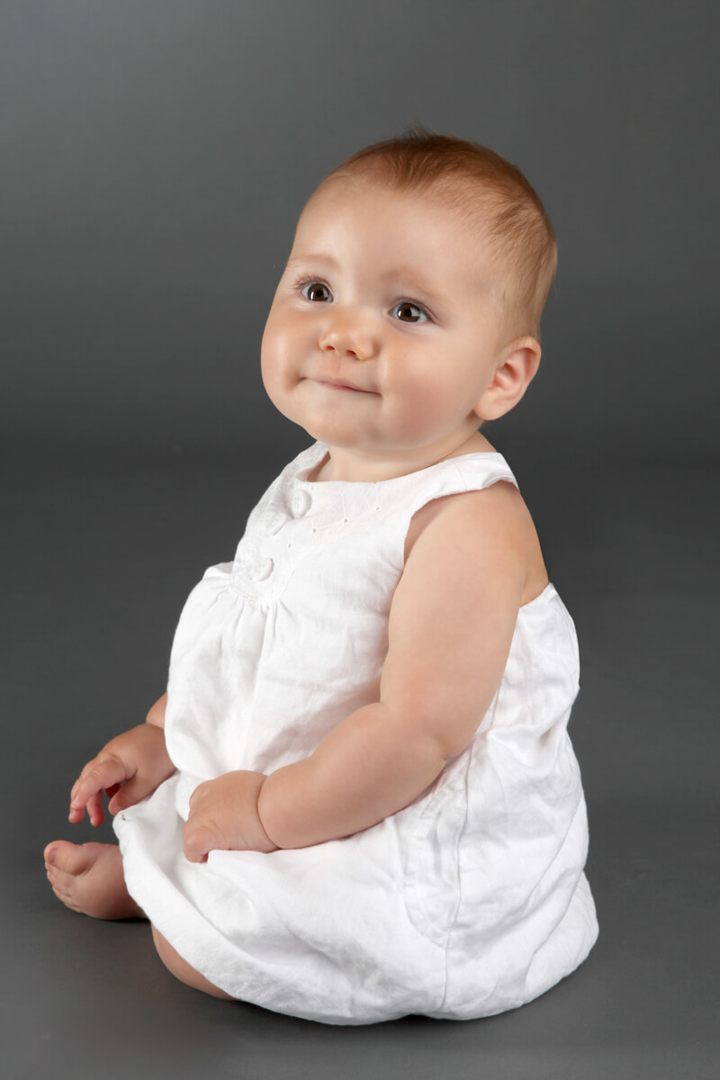 Baby poses for in-studio portrait with cute white dress