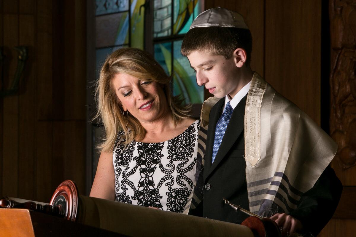 Bar Mitzvah celebrant reads torah with mother