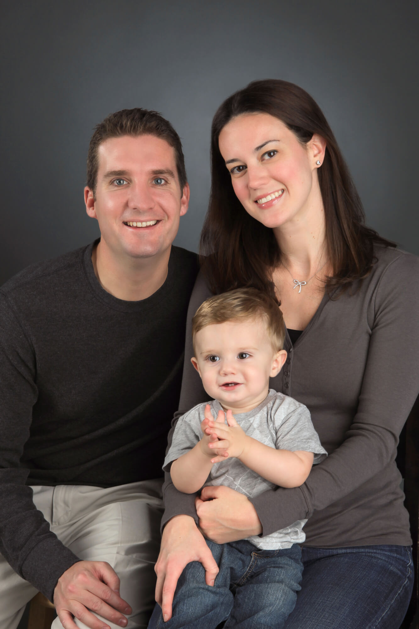 Young family posed on studio's grey backdrop