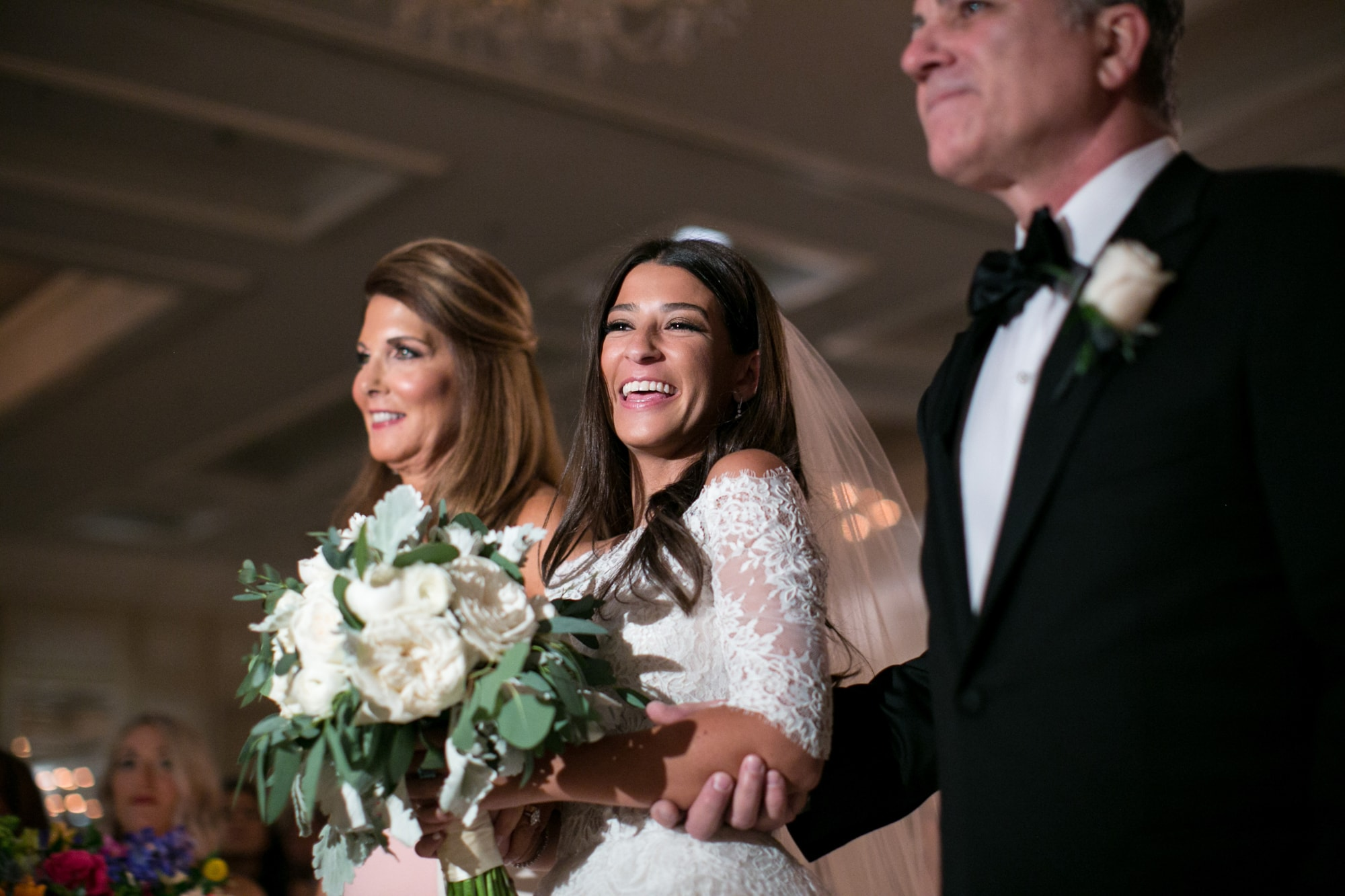Happy Bride walking down aisle with her parents.