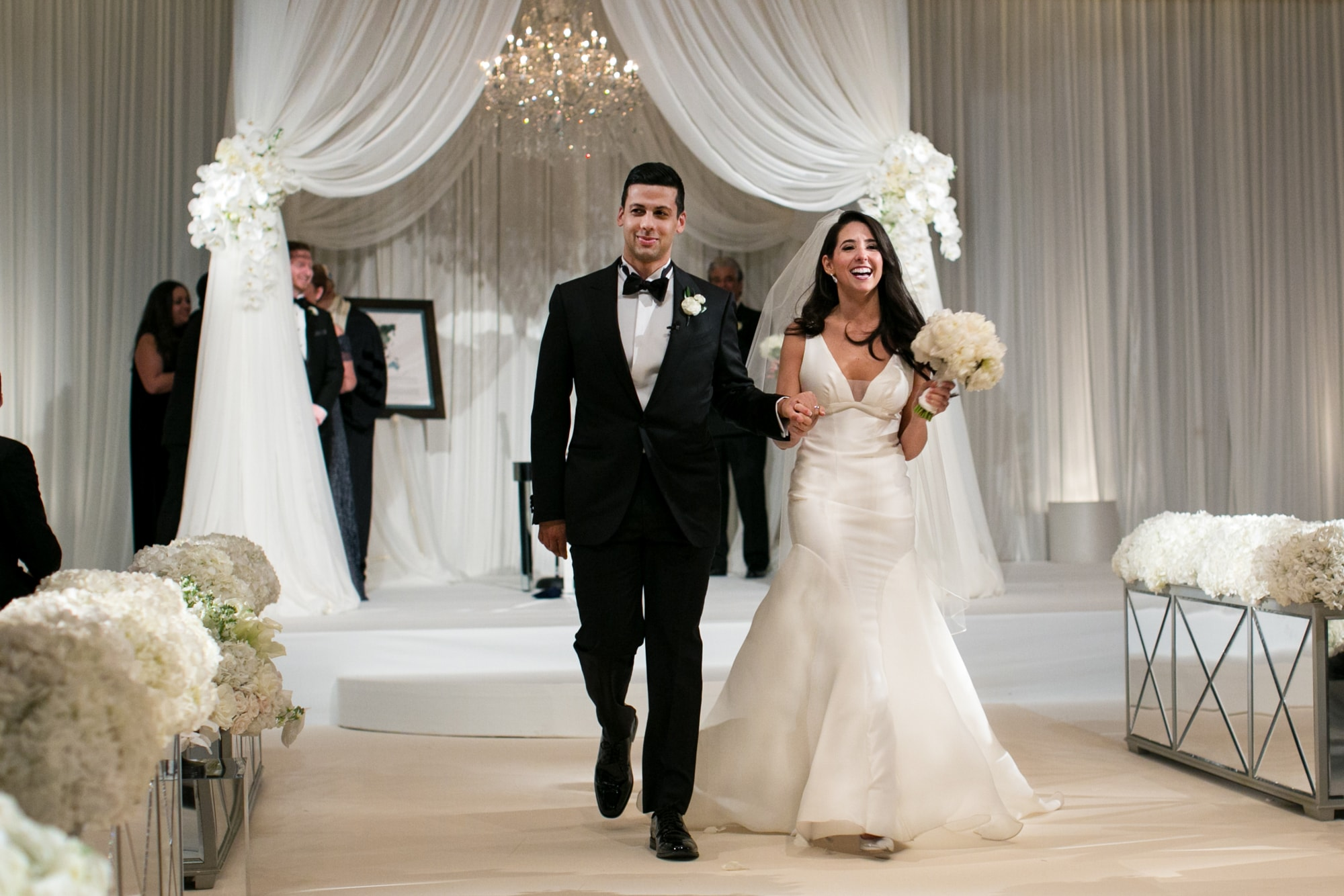 Pretty wedding recessional with white huppa