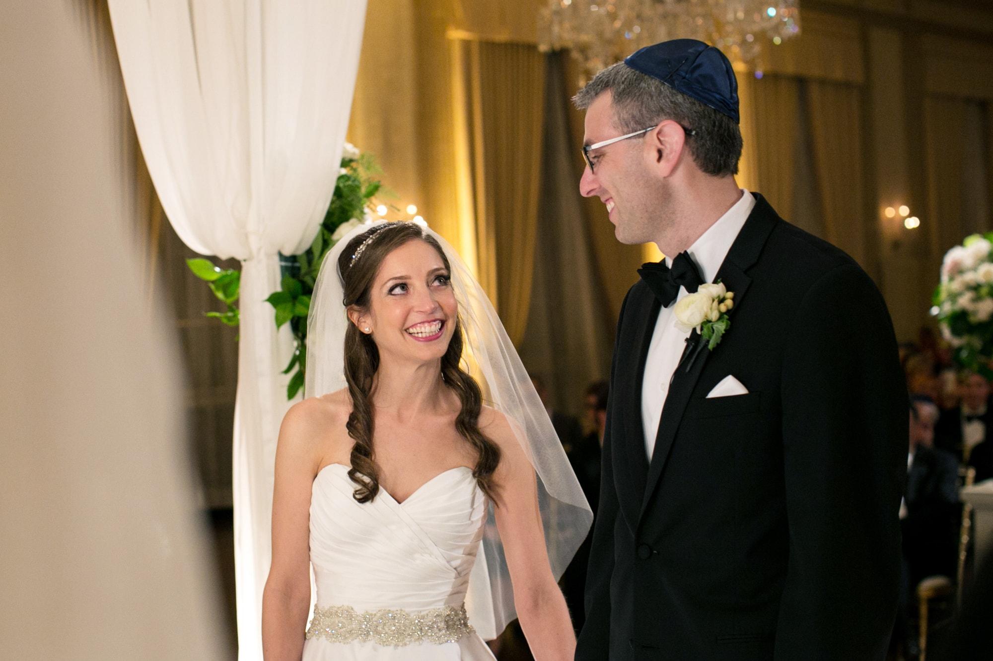 Bride and groom exchange vows under huppa at wedding ceremony