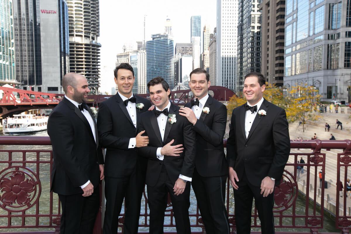 Fun portrait of groom on Chicago River bridge