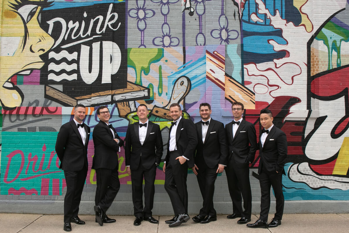 Groom poses with friends in front of graffiti wall