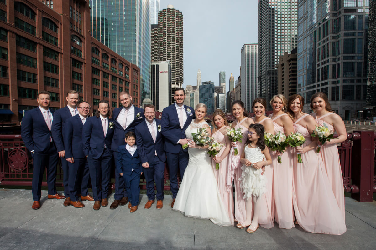 Large wedding party poses on a Chicago River Bridge