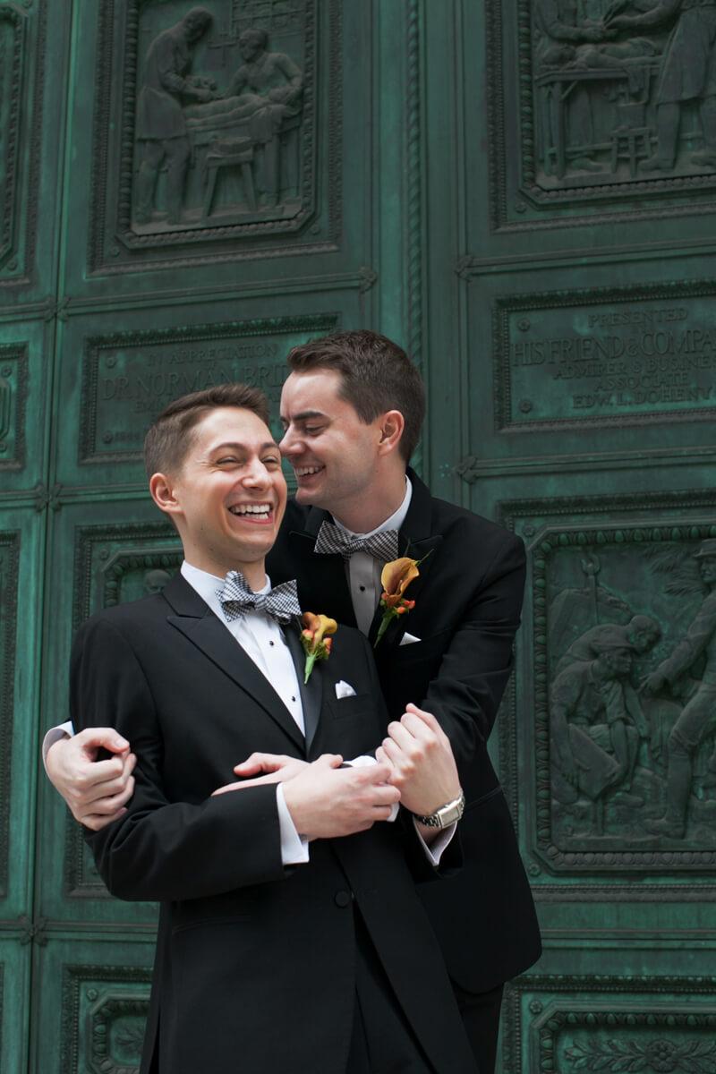 Grooms hug in front of green door of the Murphy Auditorium