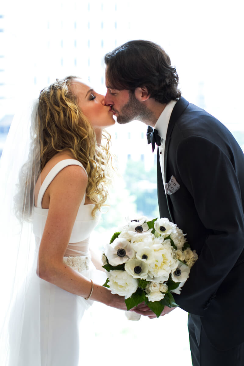 Bride and groom kissing in window light