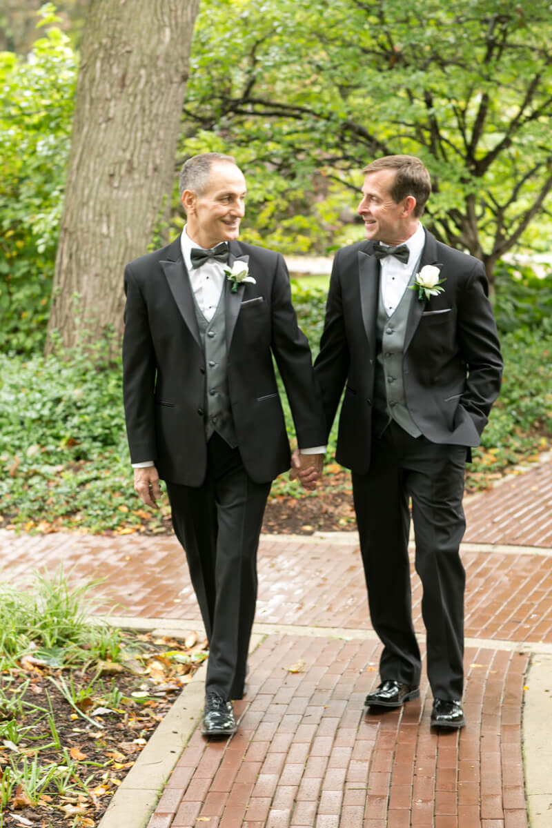 Grooms stroll down path during portrait session