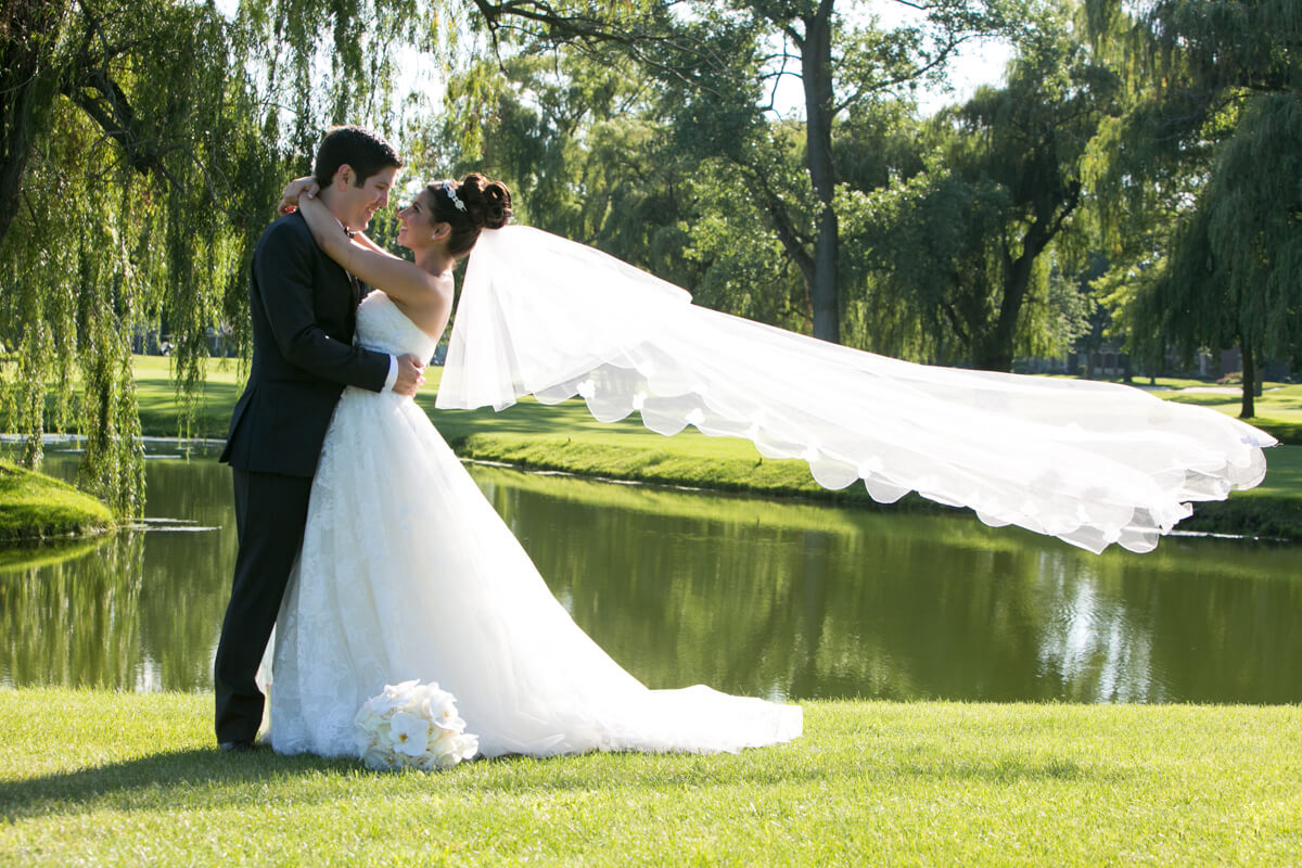 Veil blows during wedding portrait at country club