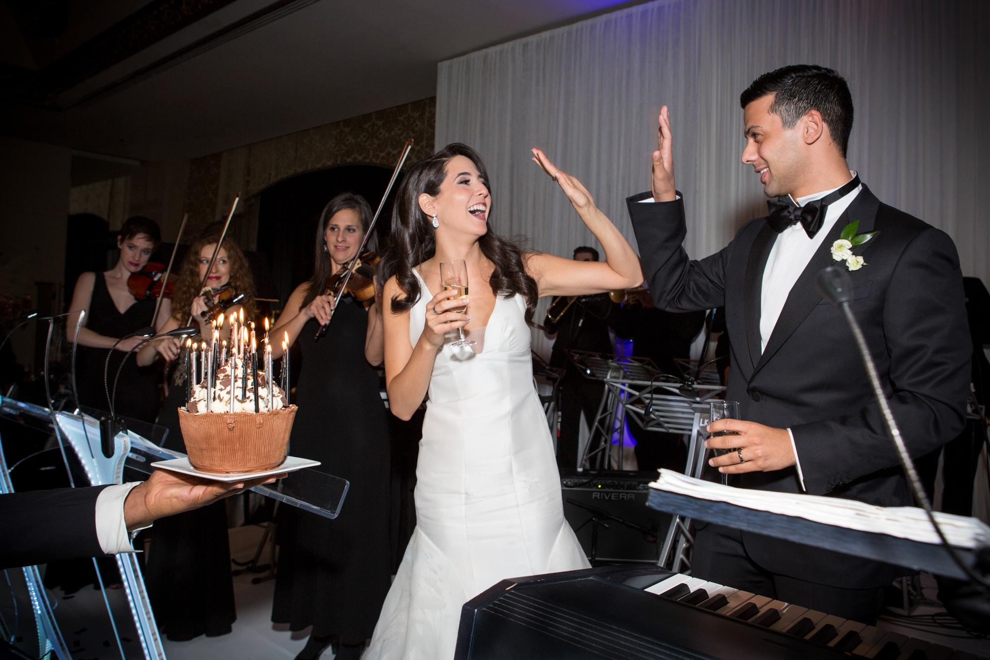 Bride receives birthday cake at wedding reception