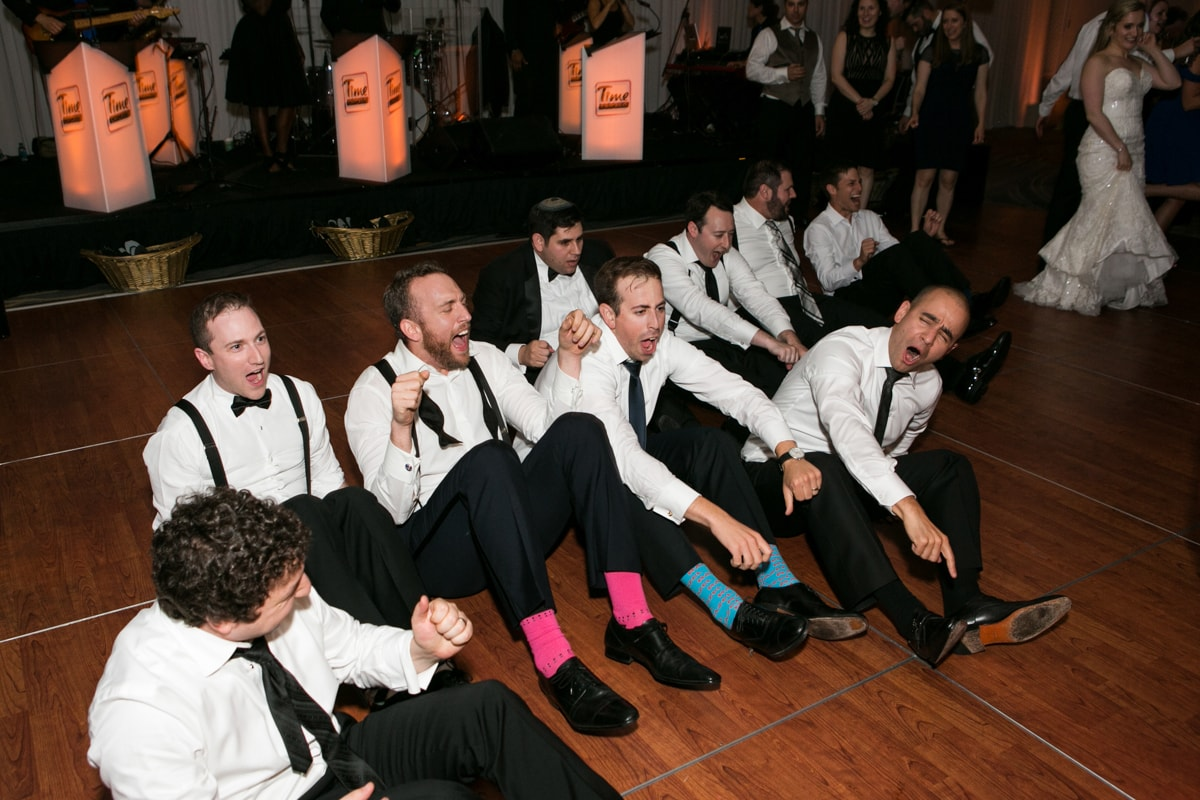 Groomsmen with fun socks dance at wedding reception