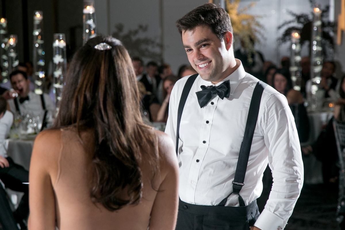 Groom smiles during toast by bride