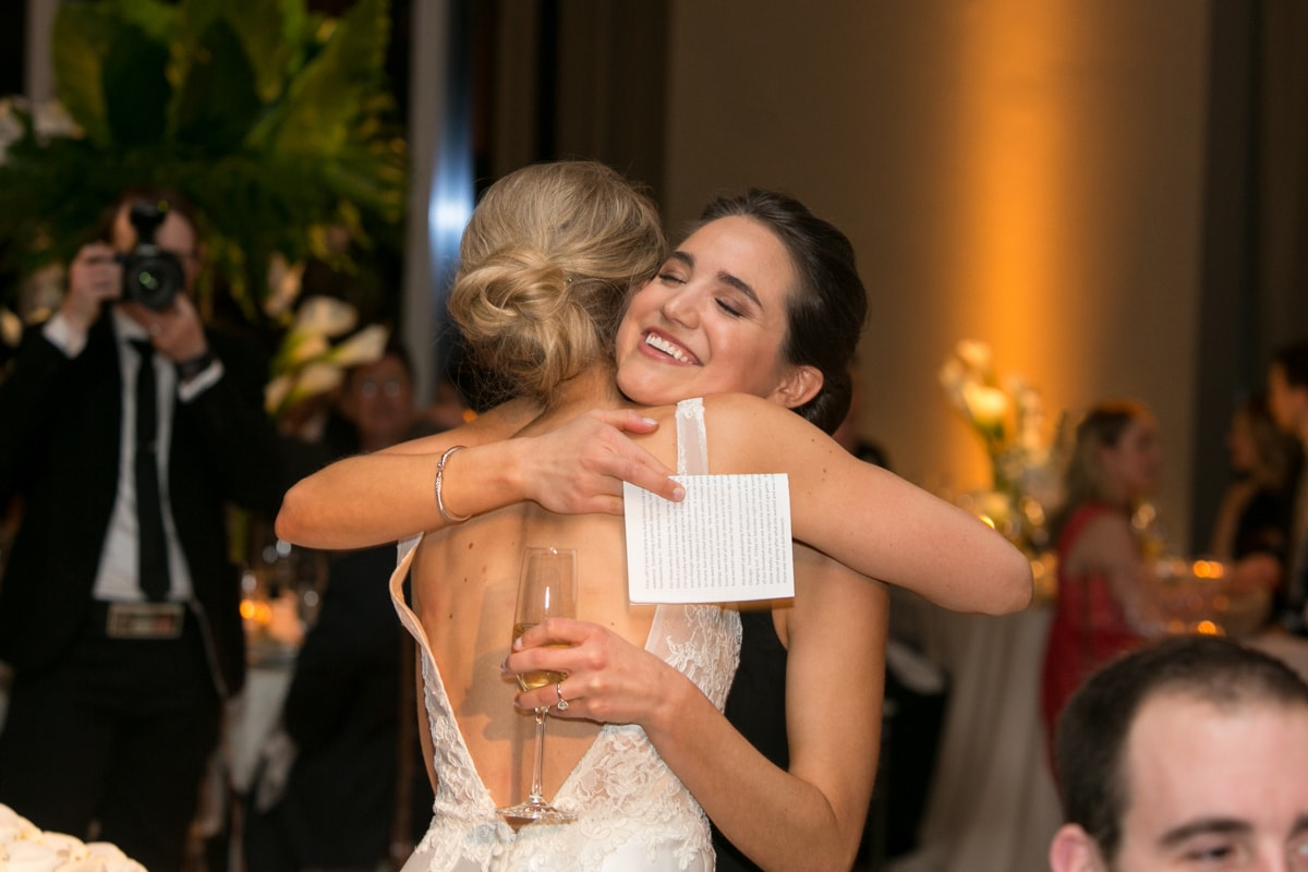 Bride hugs sister after wedding toast.