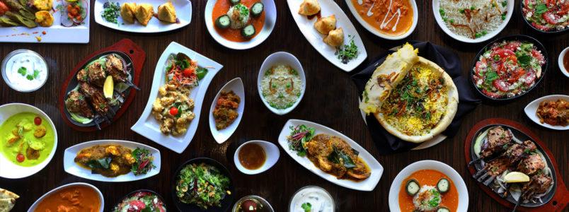 Food spread with item like Chicken Biryani, samosas, lamb rack, etc