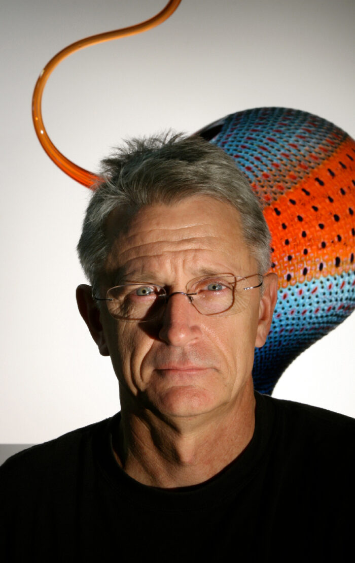 head shot of Stephen Rolfe Powell with a piece of glass art behind him