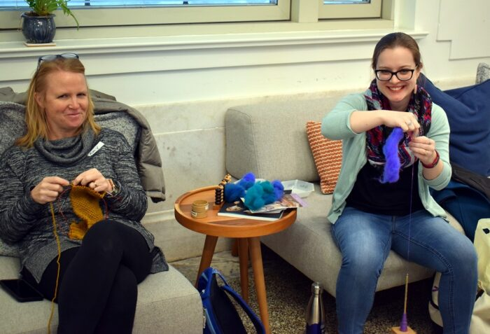 Two women knitting while sitting on couches.