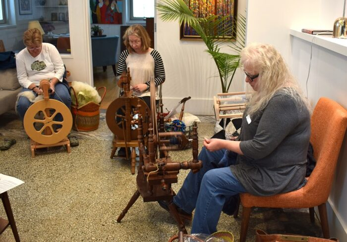 Three women using spinning wheels.