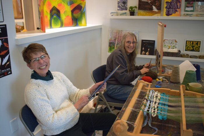 Two women using table-top looms.