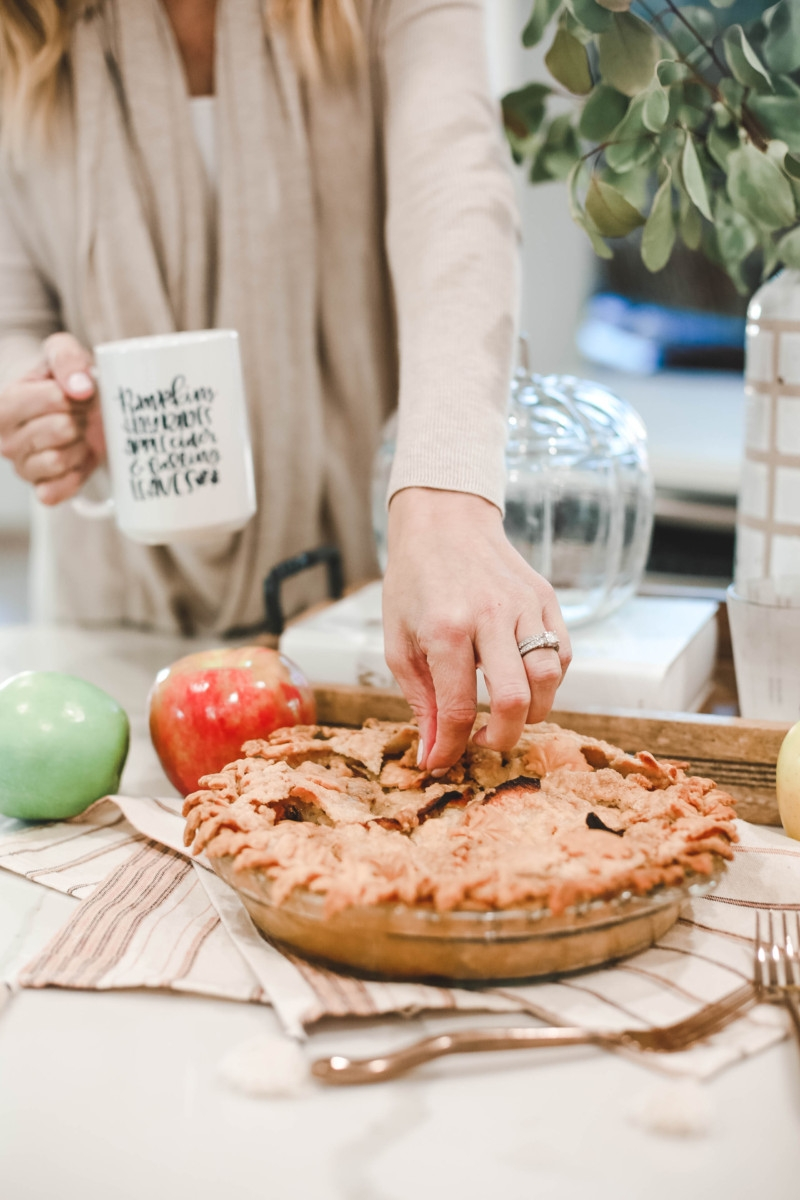 Fall | Thanksgiving | Recipes | Dessert | Mama Mary's Easy Apple Pie Recipe featured by top US lifestyle |  Mama Mary's Easy Apple Pie Recipe featured by top US lifestyle blog Haute & Humid | Easy Apple Pie Recipe by popular Houston lifestyle blog, Haute and Humid: image of a woman picking at a apple pie.