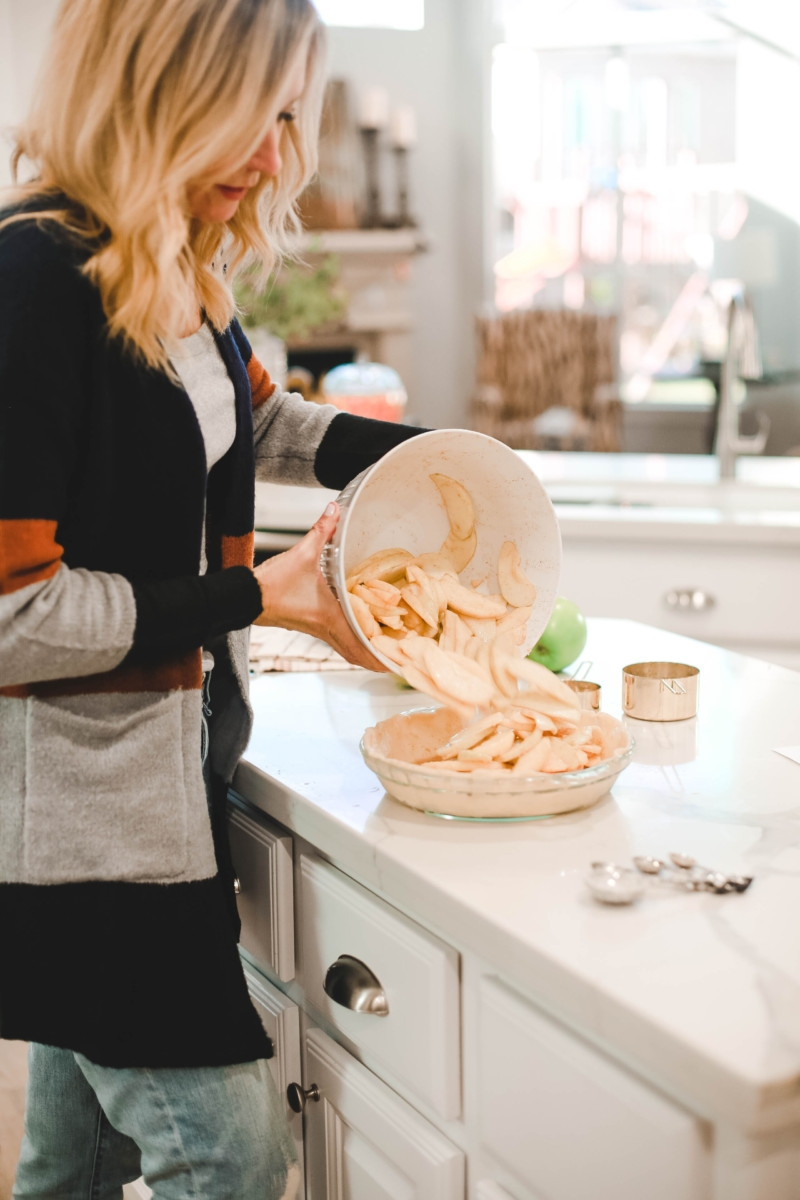 Fall | Thanksgiving | Recipes | Dessert | Mama Mary's Easy Apple Pie Recipe featured by top US lifestyle blog Haute & Humid |Mama Mary's Easy Apple Pie Recipe featured by top US lifestyle blog Haute & Humid | Easy Apple Pie Recipe by popular Houston lifestyle blog, Haute and Humid: image of a woman pouring a bowl full of sliced apples into a prepared pie crust.
