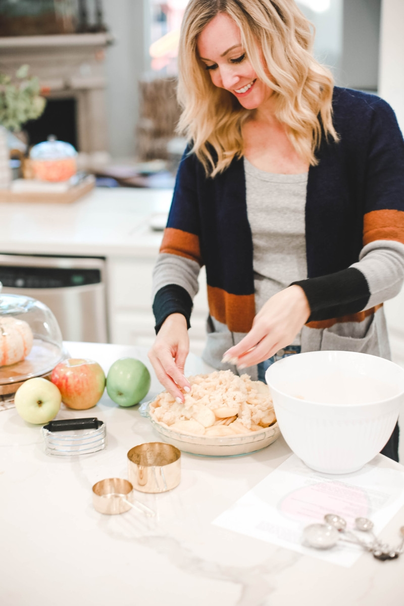 Fall | Thanksgiving | Recipes | Dessert | Mama Mary's Easy Apple Pie Recipe featured by top US lifestyle blog Haute & Humid |Mama Mary's Easy Apple Pie Recipe featured by top US lifestyle blog Haute & Humid | Easy Apple Pie Recipe by popular Houston lifestyle blog, Haute and Humid: image of a woman putting a crumb topping on a apple pie.