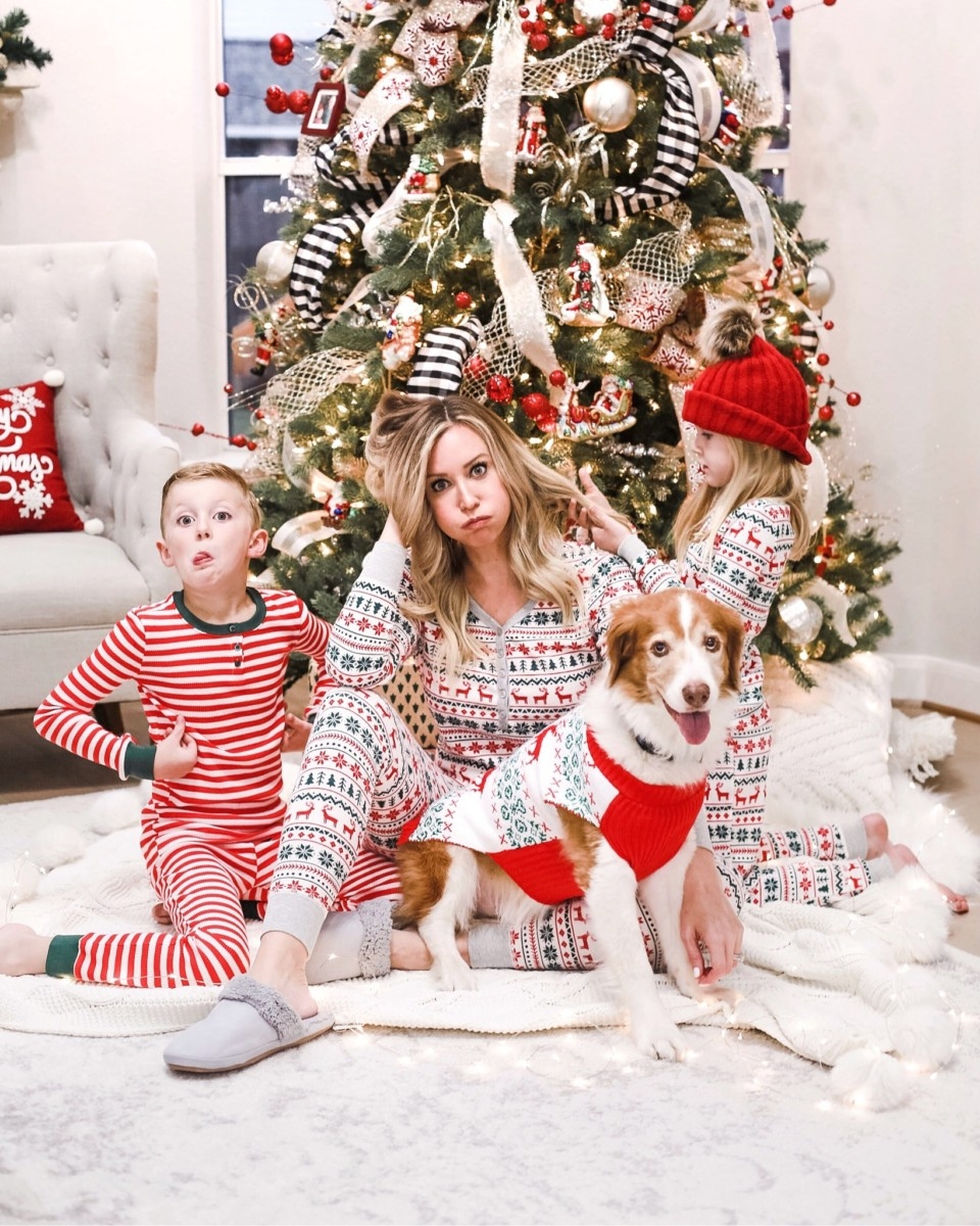 family christmas pajamas | Christmas Prep by popular Houston lifestyle blog: image of a woman and her son and daughter wearing family Christmas pajamas and sitting in front of a Christmas tree with their dog.
