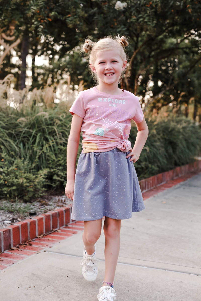 girls back to school outfit   How to Get to School on Time: 7 Easy Ways by popular Houston blog, Haute and Humid: image of a girl standing outside and wearing a Peek Aren't You Curious Solar System Graphic Tee, Peek Aren't You Curious Violet Skirt.