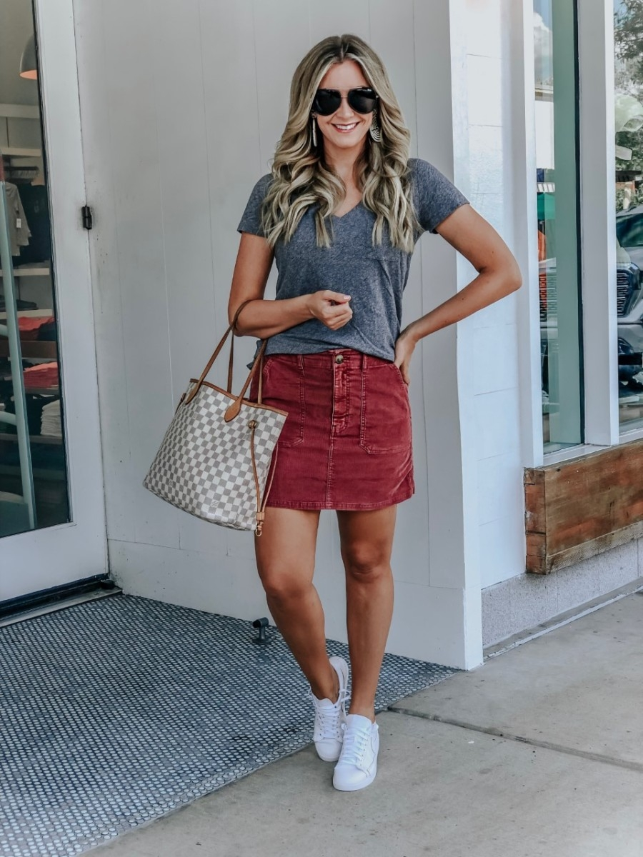 v neck tee | College Game Day Outfits by popular Texas fashion blog, Haute and Humid: image of a woman standing outside and wearing a Madewell Whisper Cotton V-Neck Pocket Tee, AE HIGH-WAISTED CORDUROY A-LINE SKIRT, Nike Blazer Low SE Sneaker, Lisi Lerch DISK - CZECH WHITE, and Quay Australia Needing Fame' 65mm Aviator Sunglasses.