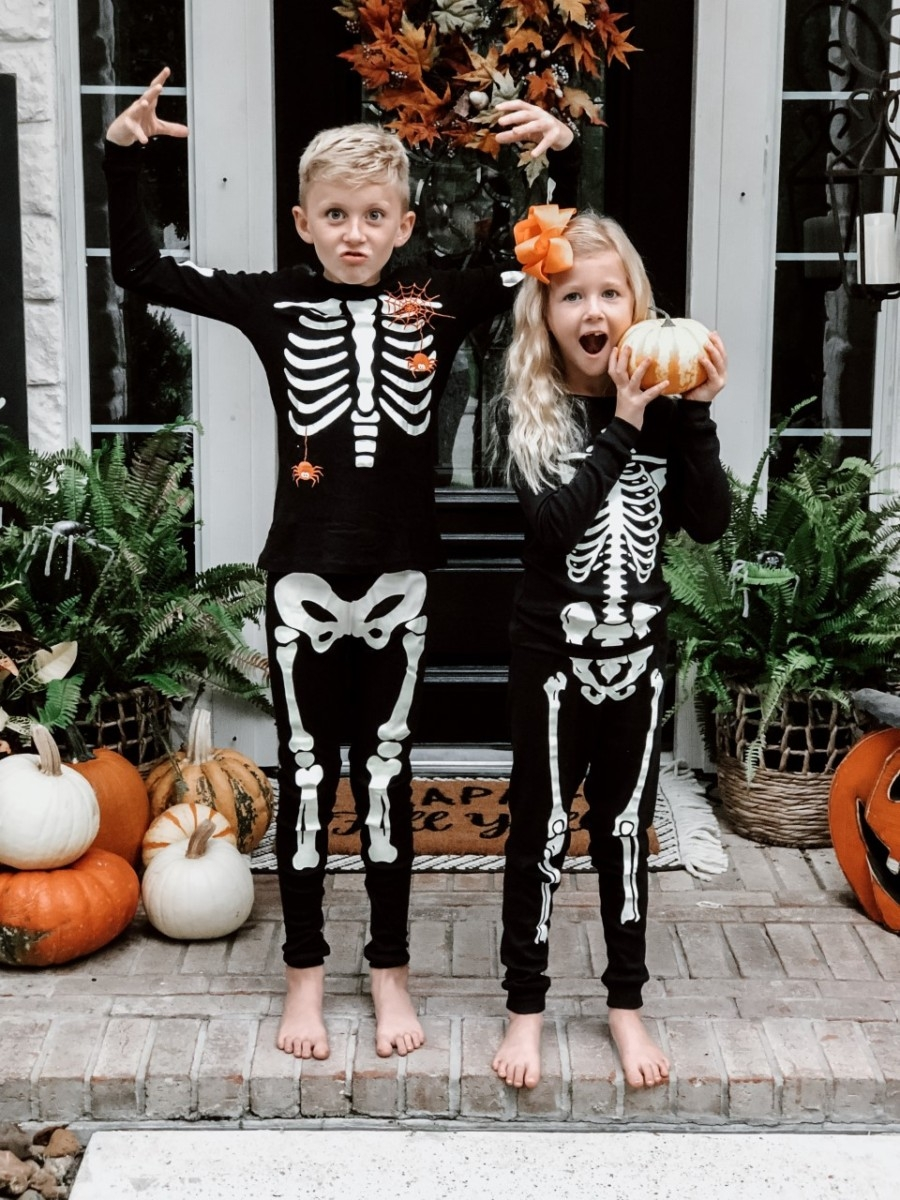 Halloween Activities | Easy Halloween Activities for Families by popular Houston lifestyle blog, Haute and Humid: image of two kids holding pumpkins on a front porch with a Target Project 62 Chevron Woven Area Rug, Etsy Happy Fall Yall Welcome Doormat, and wearing Amazon Little Pajamas skeleton glow-in-the-dark pajama sets.