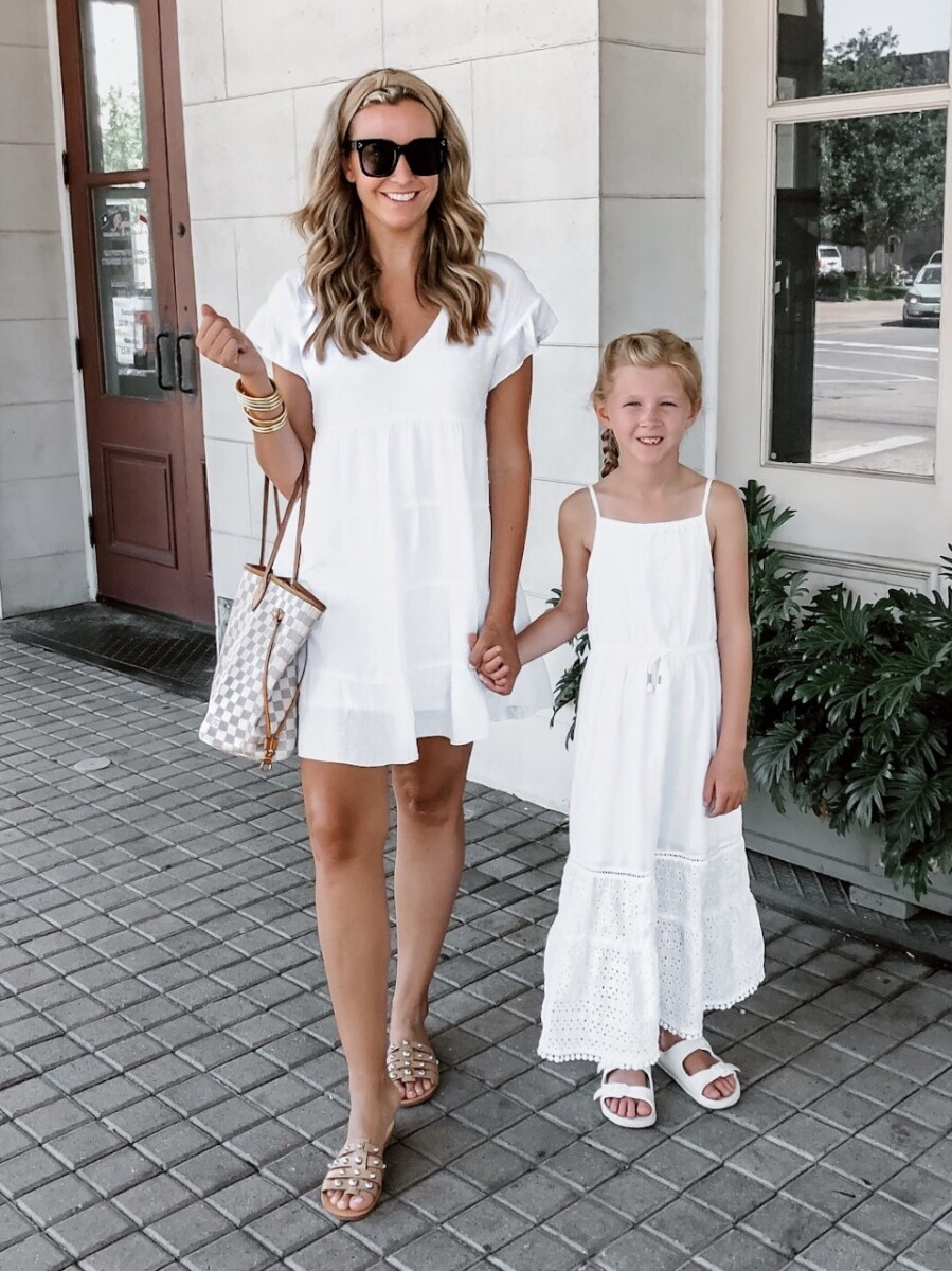 white summer dresses | White Summer Dresses by popular Houston fashion blog, Haute and Humid: image of a mom and daughter standing together and holding hands outside and wearing a Nordstrom SOCIALITE Tiered Babydoll Dress, Nordstrom MARC FISHER LTD Pava Slide Sandal, Amazon zeroUV - Retro Oversized Square Sunglasses, Budha Girl GOLD ALL WEATHER BANGLES, Amazon Funtopia Knotted Headband, and Target Cat & Jack Girls' Eyelet Maxi Dress.