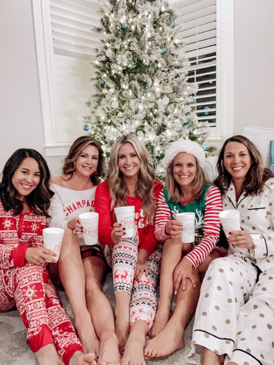 florida girls weekend |Florida Beach House Rental by popular Houston travel blog, Haute and Humid: image of four women wearing Christmas pajamas and sitting in front of a Christmas tree.