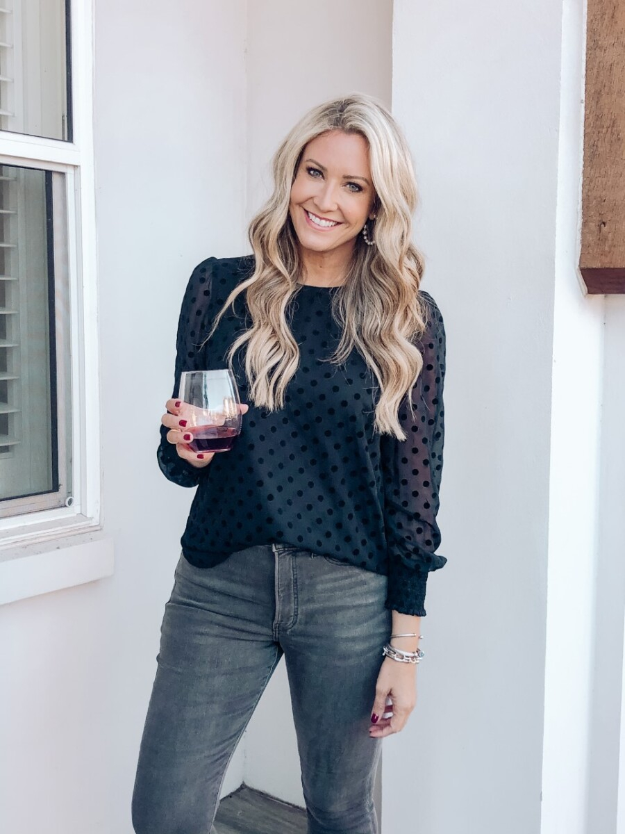 winter top |Florida Beach House Rental by popular Houston travel blog, Haute and Humid: image of a woman holding a glass of wine and wearing a sheer long sleeve blue polka dot blouse and jeans.