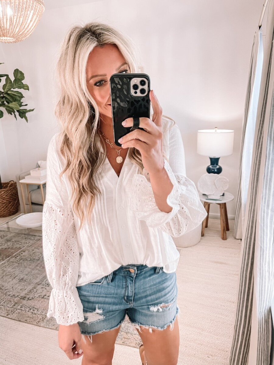 white eyelet top  Amazon Favorites by Houston life and style blog, Haute and Humid: image of a woman wearing a Amazon white eyelet top and a pair of denim cut off shorts.