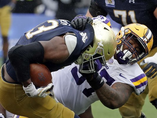 LSU defensive end Frank Herron, right, tackles Notre Dame running back Josh Adams during the first half of the Citrus Bowl NCAA college football game, Monday, Jan. 1, 2018, in Orlando, Fla. (AP Photo/John Raoux)