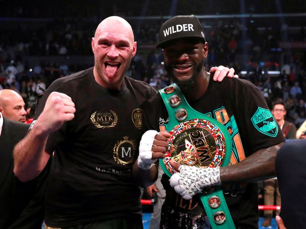 Deontay Wilder standing with Tyson Fury