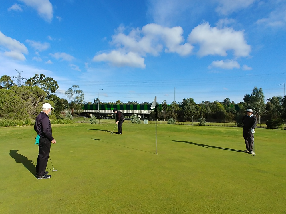 John Mathews putts, watched on by Dave Rogers left and Taff Davies