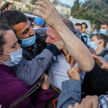 دست به یقه شدن یک پلیس اسرائیلی با عوفر کاسیف نمایندهٔ مجلس اسرائیل «کنست» (نفر وسط)، عضو یهودی ائتلاف انتخاباتی به طور عمده عرب «فهرست مشترک»، در جریان تظاهراتی علیه اشغال و شهرکسازی اسرائیل. (عکس از احمد غرابلی/خبرگزاری فرانسه)