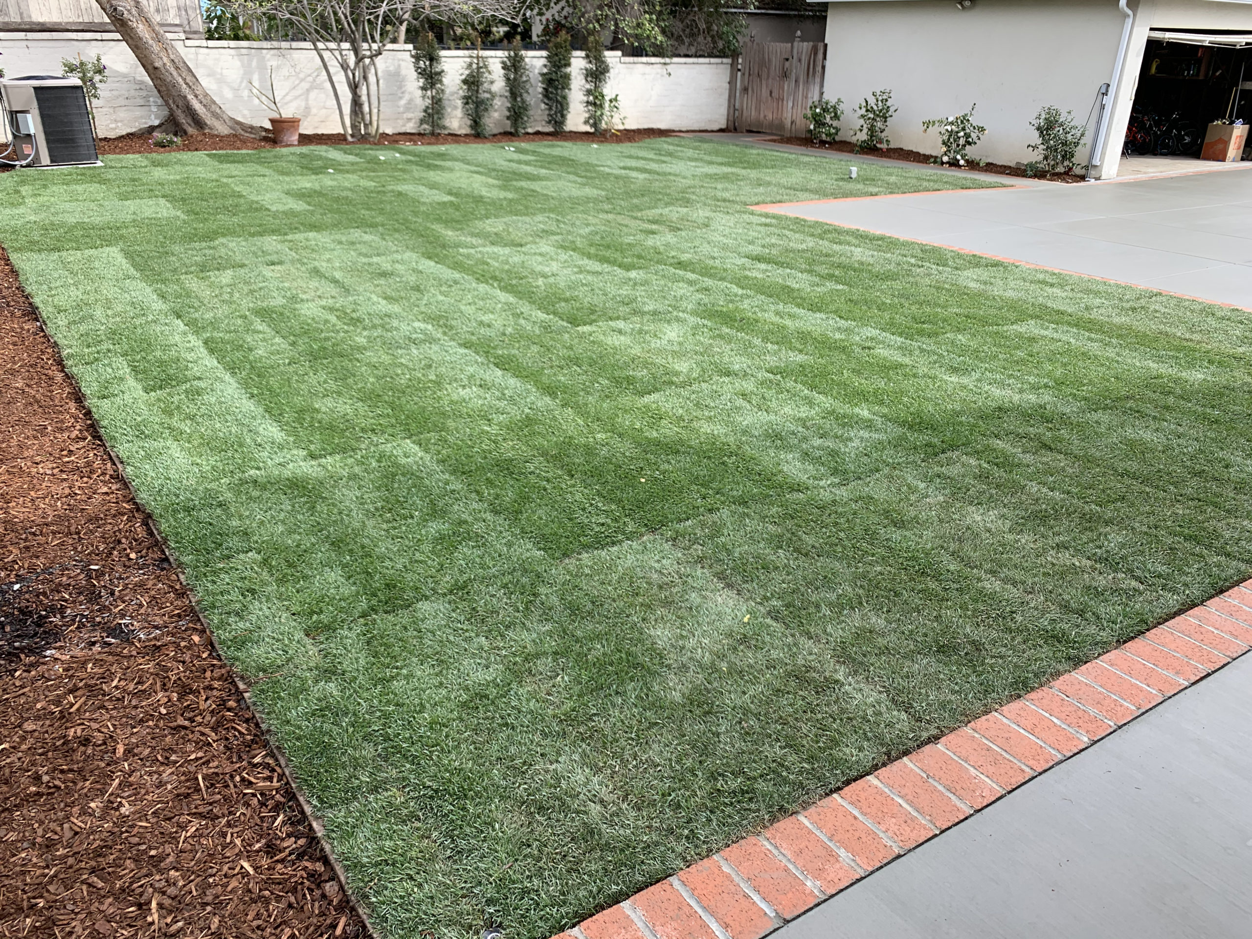 Sod-and-cement-patio-with brick trim by Eds Landscaping