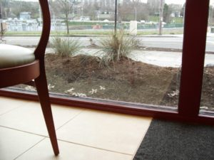 """""""Just keep piling on the mulch. The windows will keep it in place"""". This planting bed was not intended to be a berm."""