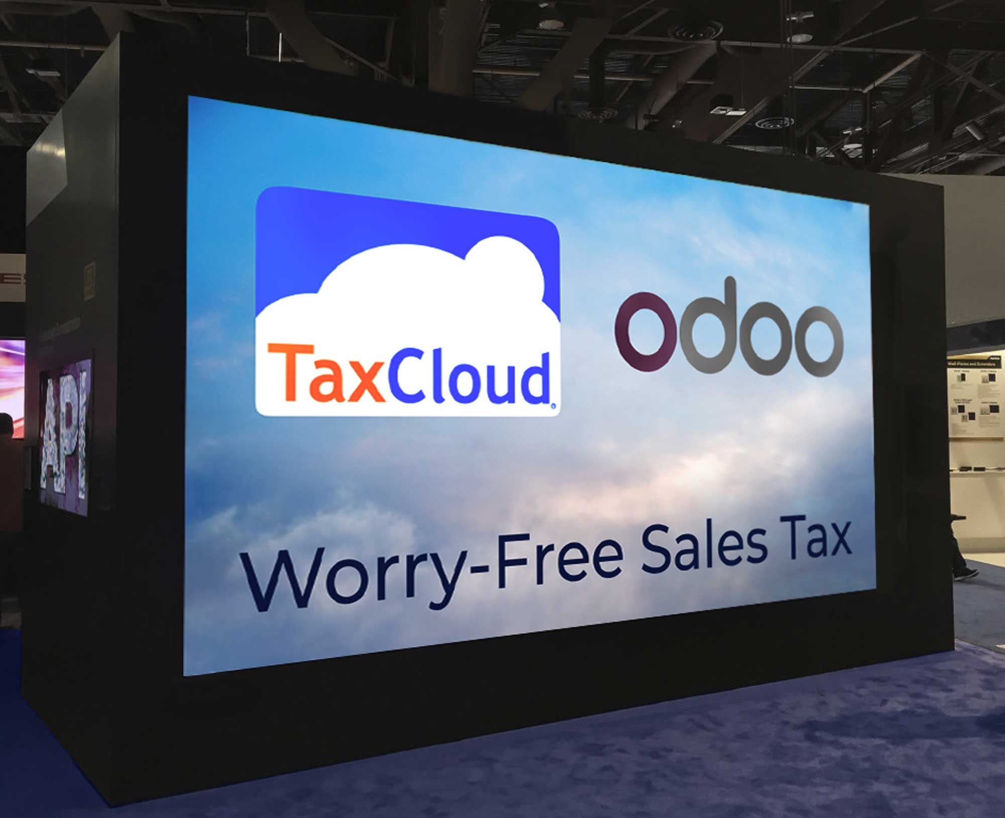 View of a trade show booth with a large TaxCloud and Odoo video playing made by UX/UI Designer Priscilla Prentice