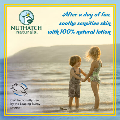 Two children holding hands on the beach and smiling - Nuthatch naturals skin care for kids