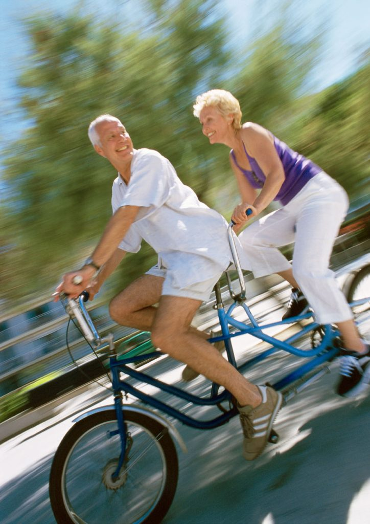 AWNM29 Mature man and woman riding together on tandem bike, side view, blurred