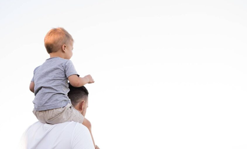 young boy sitting on top of fathers shoulders
