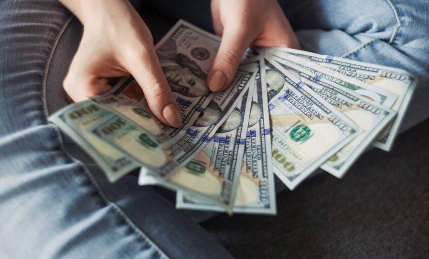Person holding hundred dollar bills in hand