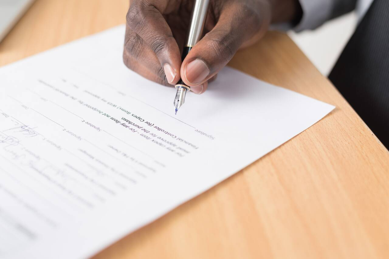 Man signing paperwork with pen