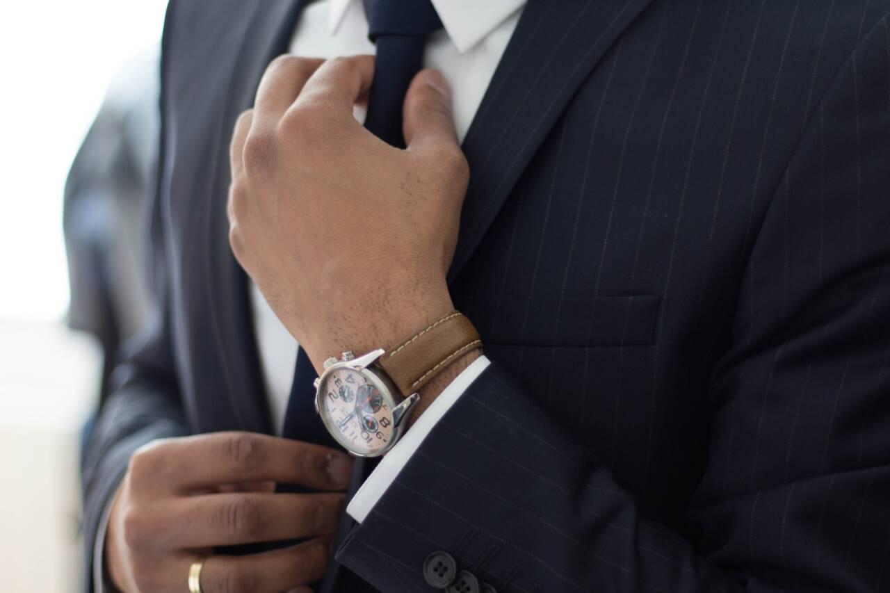 man fixing suit tie