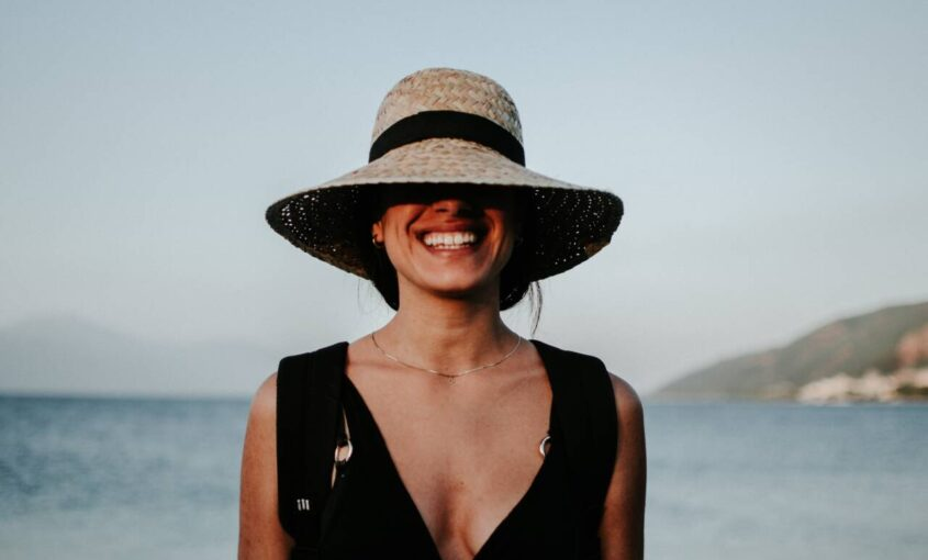 woman with hat over face
