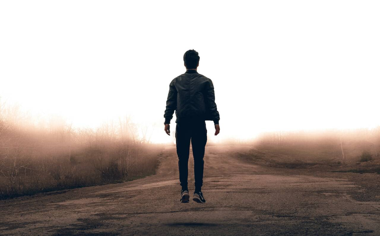 man walking on dirt path