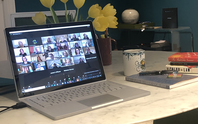 Photo of laptop showing Zoom meeting with notebook and coffee cup